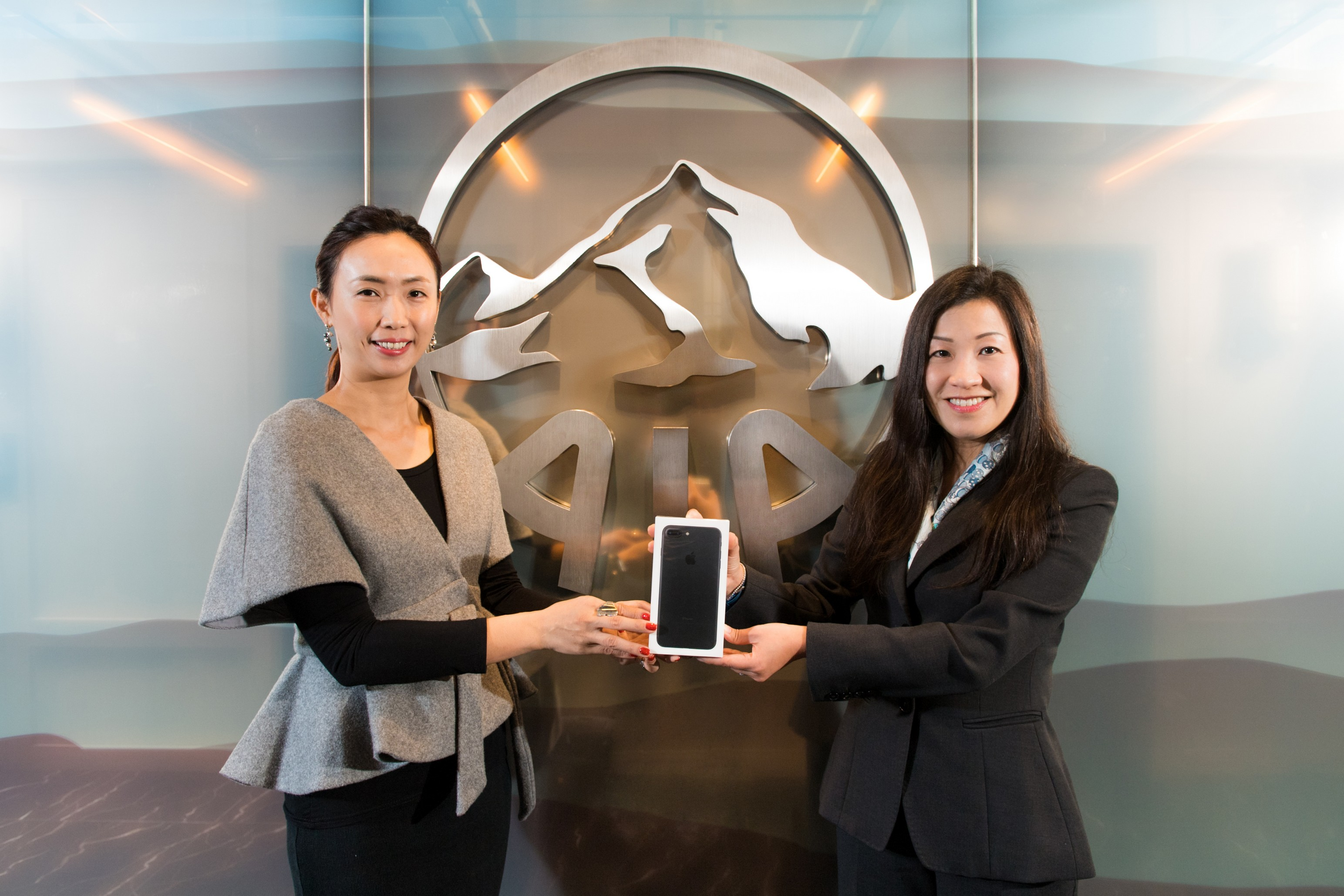 Ms Bonnie Tse, General Manager, Business Strategy and Marketing of AIA Hong Kong & Macau (right) presents the latest smartphones to the two winners of the first week's AIA Vitality Weekly Challenge Lucky Draw.